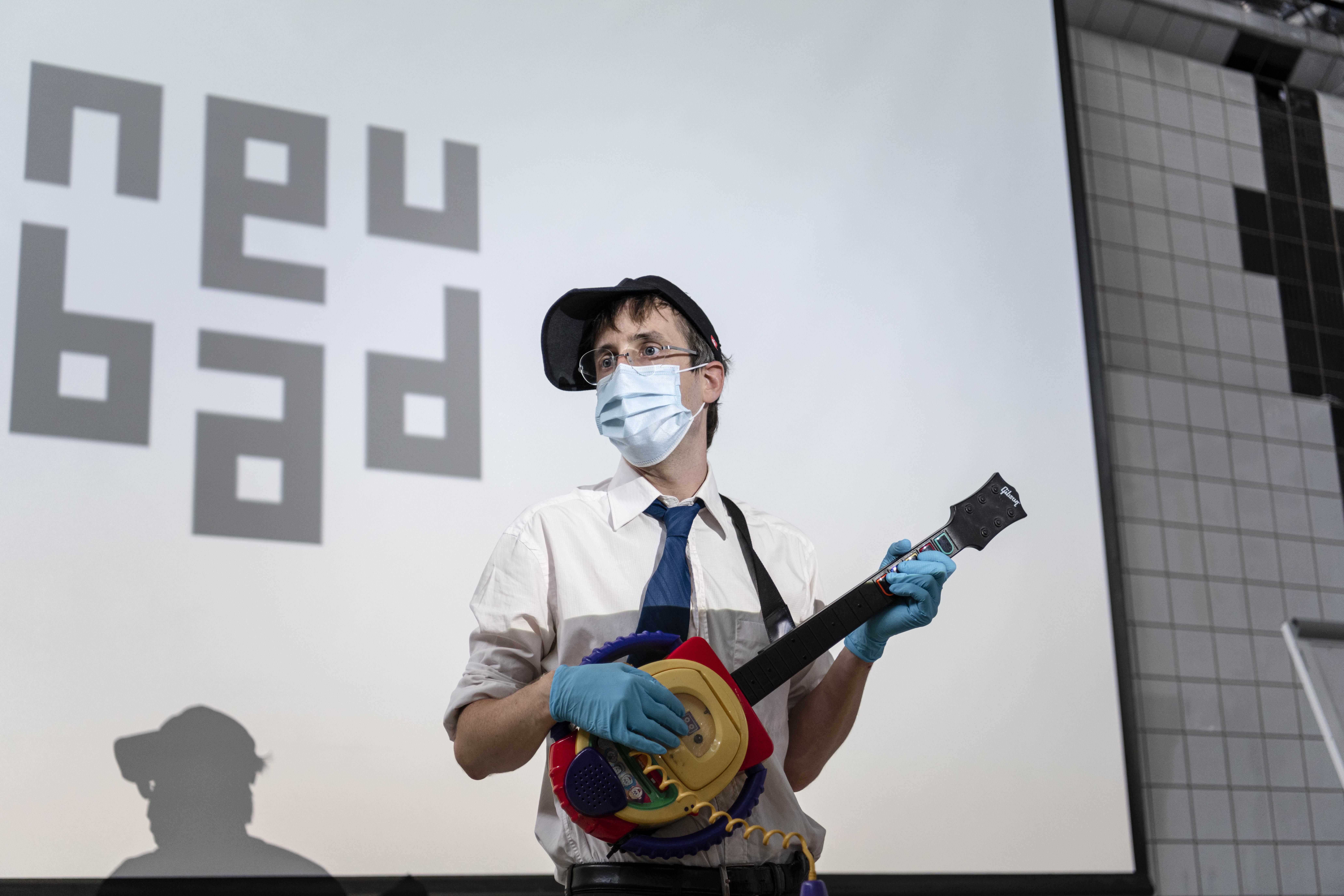 Der Anlass hat im Neubad stattgefunden und hier sieht man hinter mir mit Cap, Instrument, Maske und Handschuhe ihr Logo im Hintergrund.